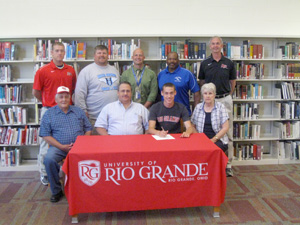 Gallia Academy's Tim Warner poses with family and coaches after signing to continue his career at Rio Grande