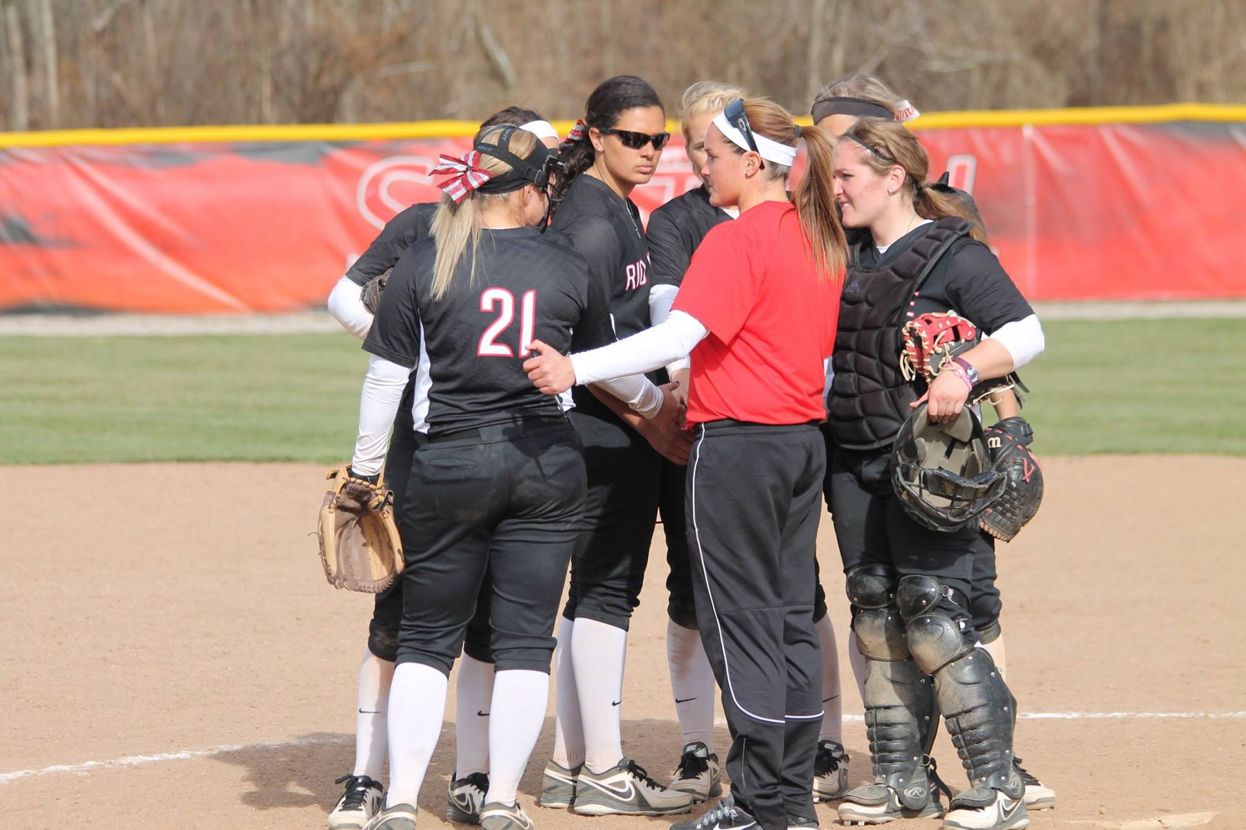 Kristen Bradshaw (red shirt) talks with her players during a break in a game earlier this spring