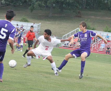 Rio's Cesar Lopez tries to fend off a Taylor defender in the RedStorm's shutout win over the Trojans.