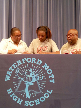 Waterford Mott High's Connie Cogdell signs with Rio Grande as her parents, Avonda and Therman look on