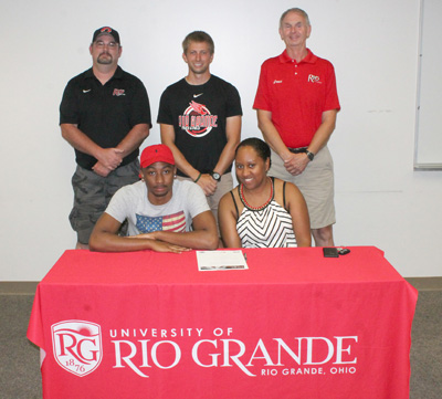 Tiffin University transfer Juan Cummings poses with his mother and Rio coaches before signing with the RedStorm