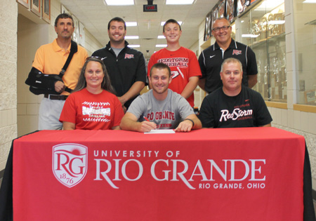 Portsmouth West High's Brady Knittel is joined by family and coaches as he prepares to sign with Rio Grande