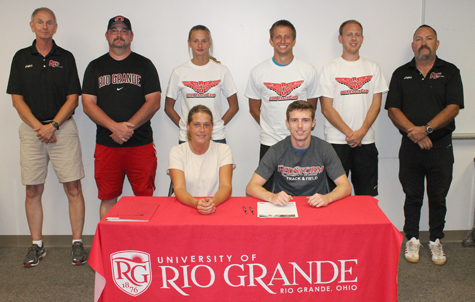 Williamsburg High's Cody Minnie is joined by his mother, Sharon, and Rio coaches as he signs with the RedStorm