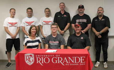 Adena High's Max Putnam is joined by his parents and Rio Grande coaches as he sets to sign with the RedStorm