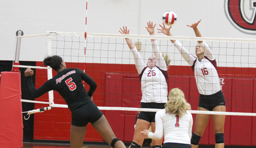 Rio's Madison Wilson sends a volley through IU-Southeast's Hannah Barker (25) and Katie Fischer (16)