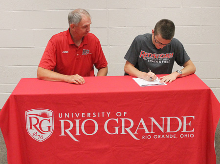 Rio coach Bob Willey watches as Valley High's Alex Craft signs with the RedStorm