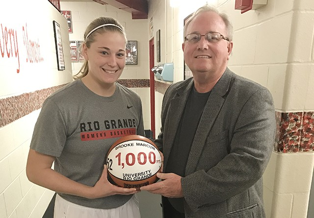 Rio Grande senior Brooke Marcum is presented with a commemorative ball by coach David Smalley after surpassing the 1,000-poin