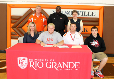 Nelsonville-York's Isaac Andrews poses with family, coaches and administrators after signing with Rio Grande