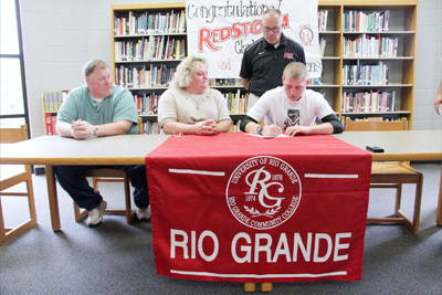 Lawrence County High's Brandon Stevens signs with Rio Grande as his parents and Rio head coach Brad Warnimont look on