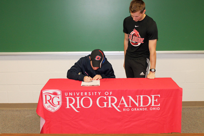 Rio assistant coach Steve Gruenberg watches as Oak Hill's Tim Haag signs with the RedStorm