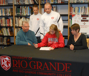 Dixie Heights High's Ashley Meek signs with Rio Grande women's soccer as her parents and RedStorm coaches look on